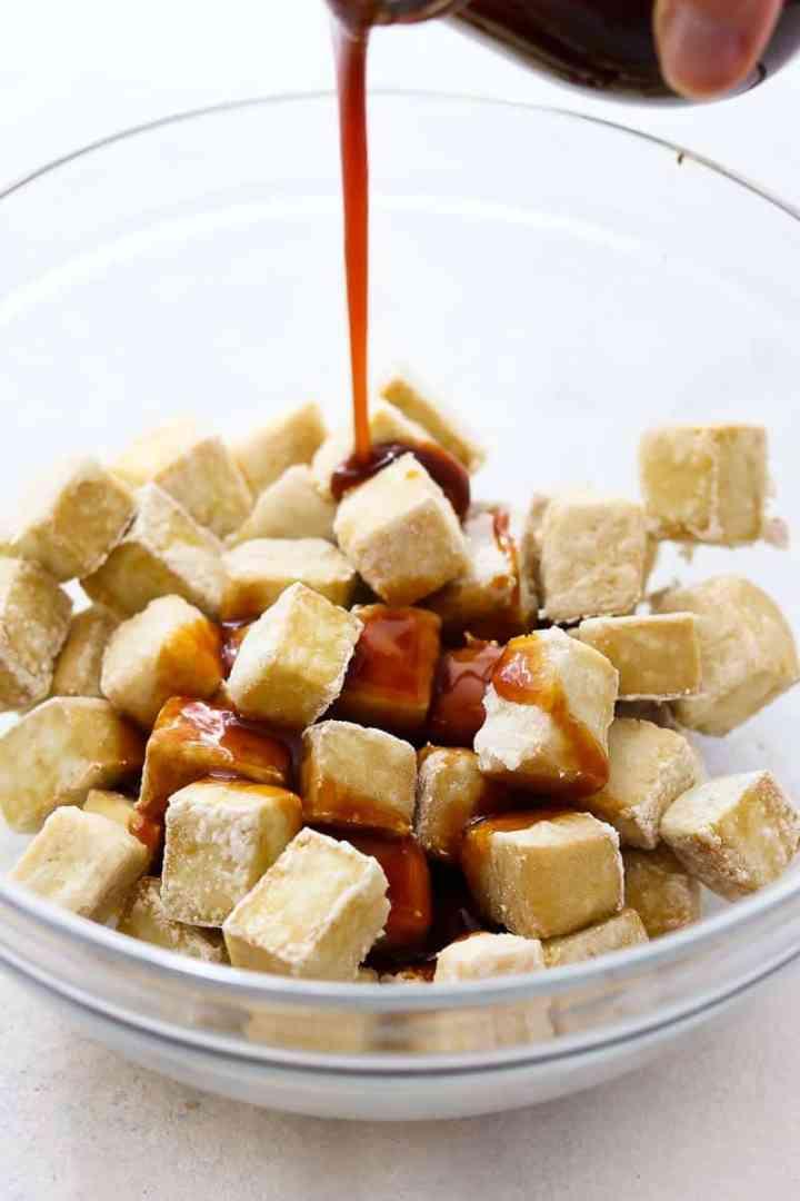 Crispy baked tofu with teriyaki sauce pouring on top.