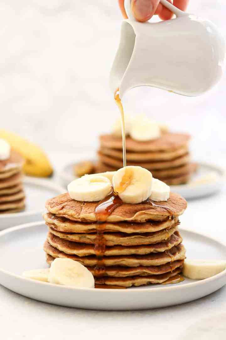 Stack of banana pancakes with maple syrup poured on top.