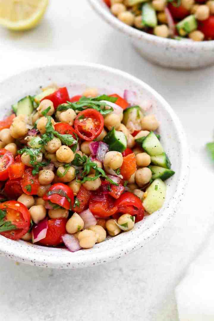 Up close of chickpea salad with fresh basil.