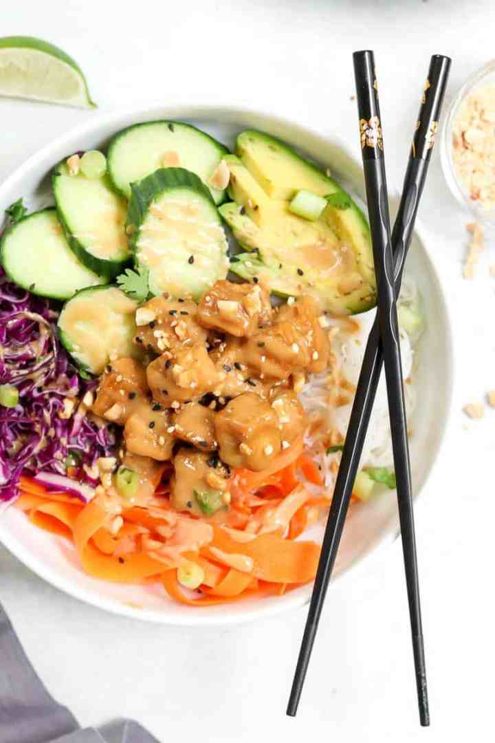 Overhead shot of buddha bowl with peanut tofu and black chopsticks.