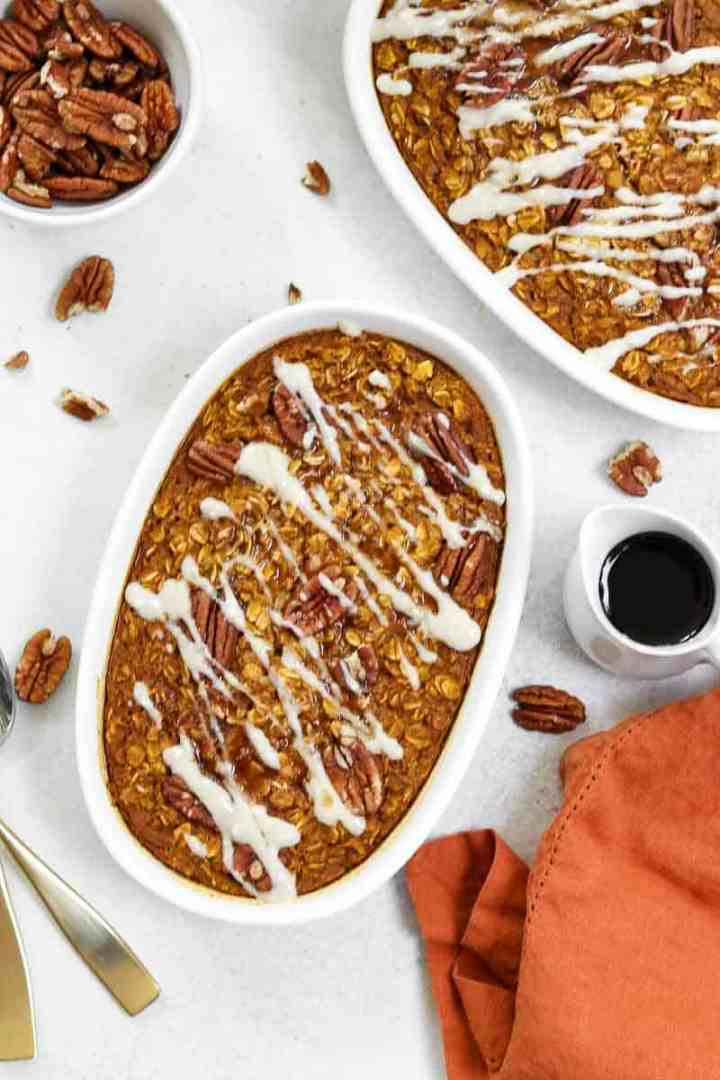 Two white dishes with pumpkin oatmeal and cream cheese glaze.