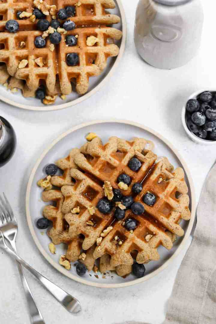 Overhead shot of almond flour waffles on a blue plate with blueberries on top.