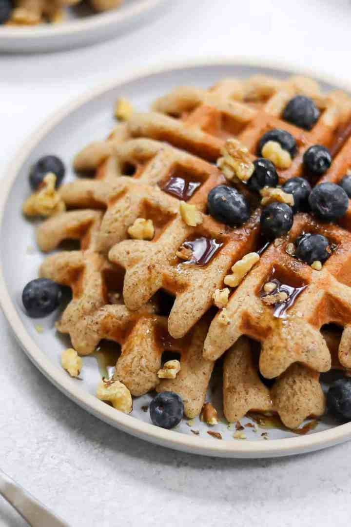 Almond Flour waffles with maple syrup, blueberries and crushed walnuts.