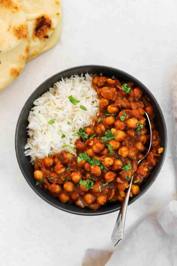 Vegan chana masala in a black bowl with white rice.