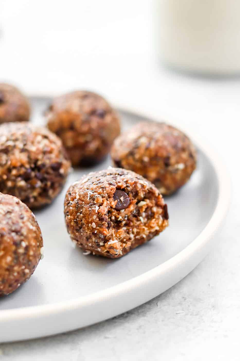 almond butter Energy balls on a blue plate with a bite taken out.