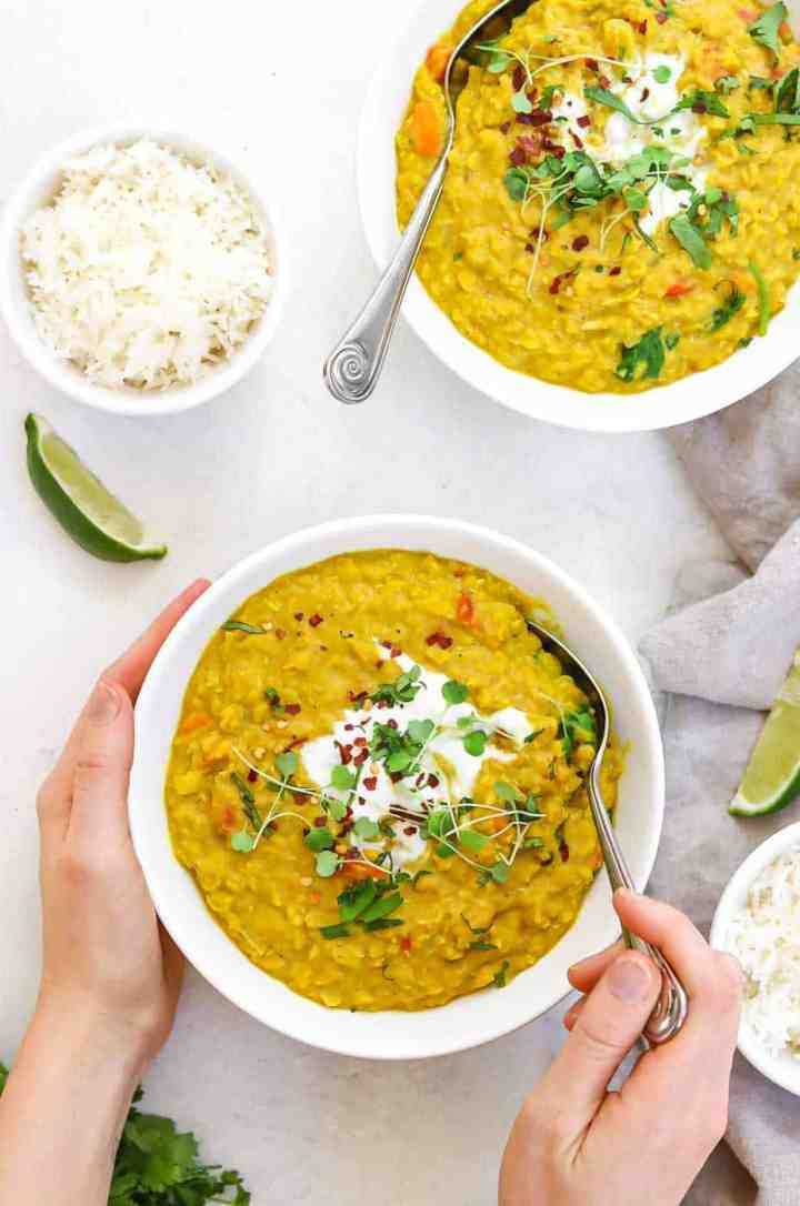 Two bowls of dal with hands grabbing a bite.