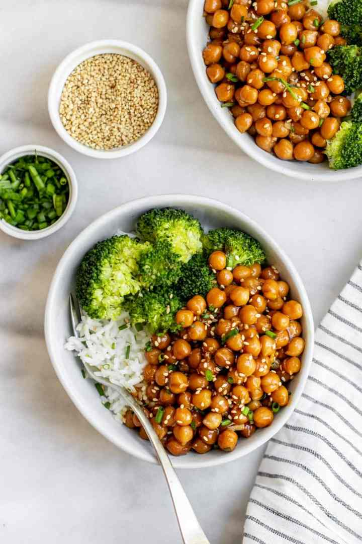 Hands holding a bowl with sesame chickpeas.