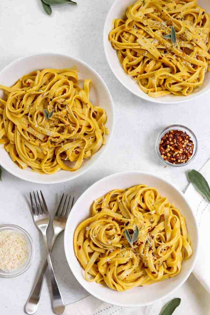 Three bowls of pumpkin pasta with sage on top.