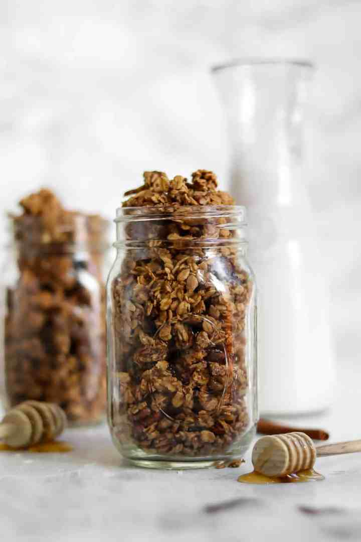 Mason jars with granola and two honey spoons.