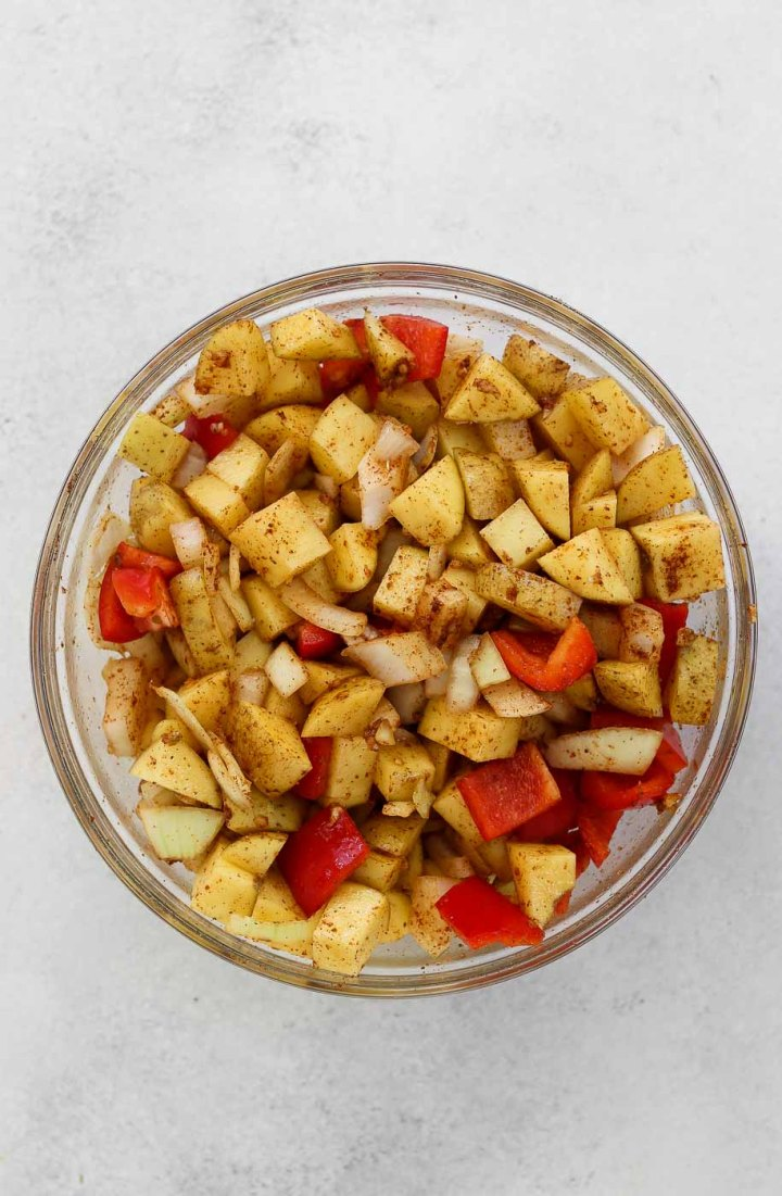 Chopped and seasoned vegetables in a glass bowl.