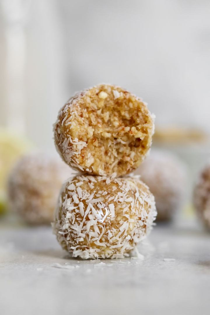 Two healthy bliss balls stacked on each other with one bite taken out.