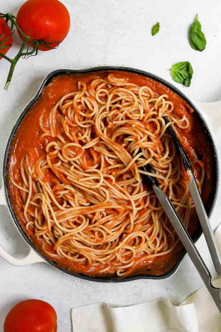 Vegan spaghetti in a pan with red sauce on top.