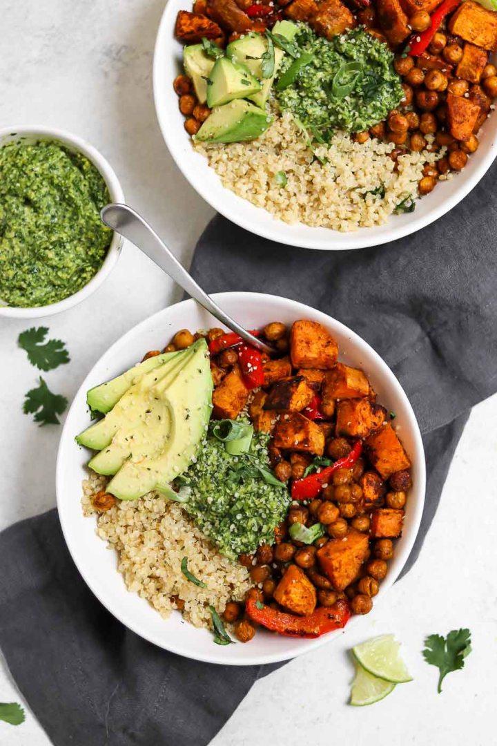 Quinoa, sweet potato, chickpeas, pesto, and avocado in a white bowl.