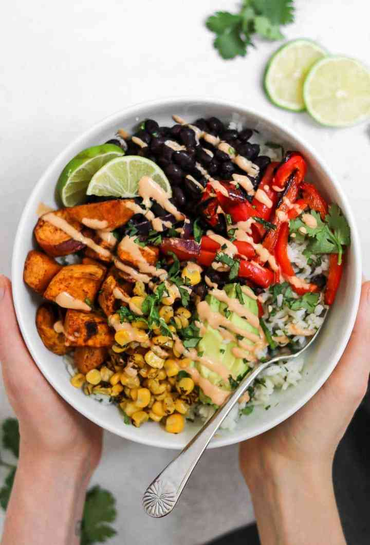 Hands holding white bowl with burrito bowl ingredients.