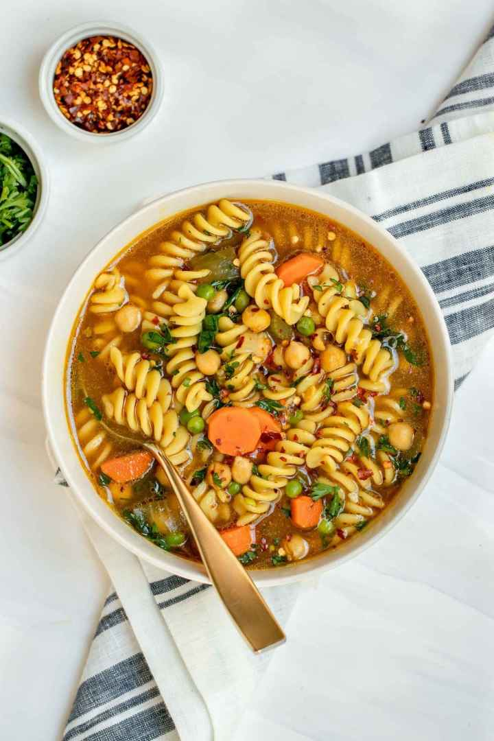 Chickpea noodle soup with a gold spoon on the side.