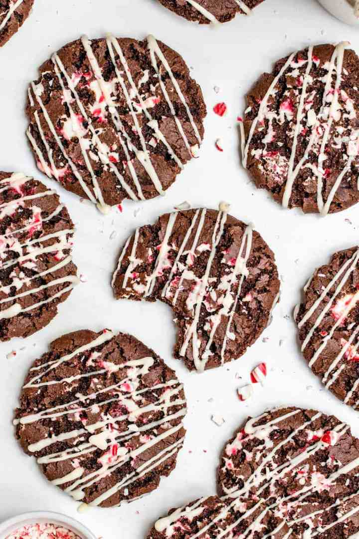 Chocolate peppermint cookies with a bite taken out on a white backdrop.