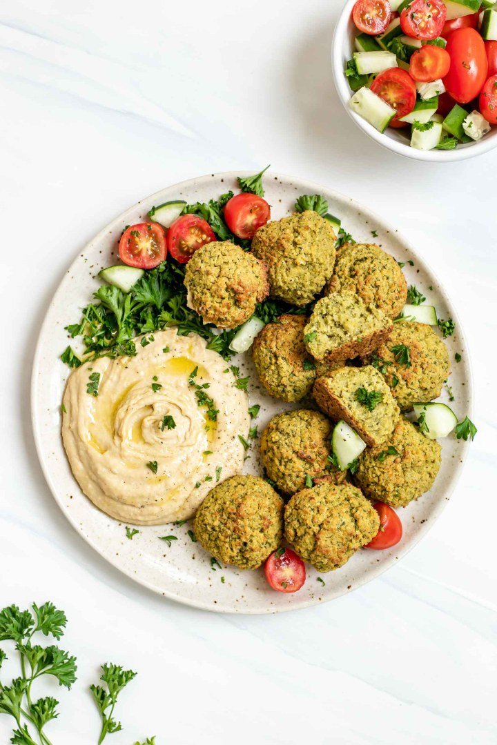 Plate with baked falafel, hummus, cucumber and tomatoes.