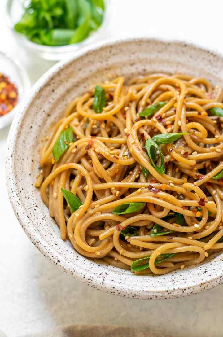 Up close of garlic sesame noodles with scallions.