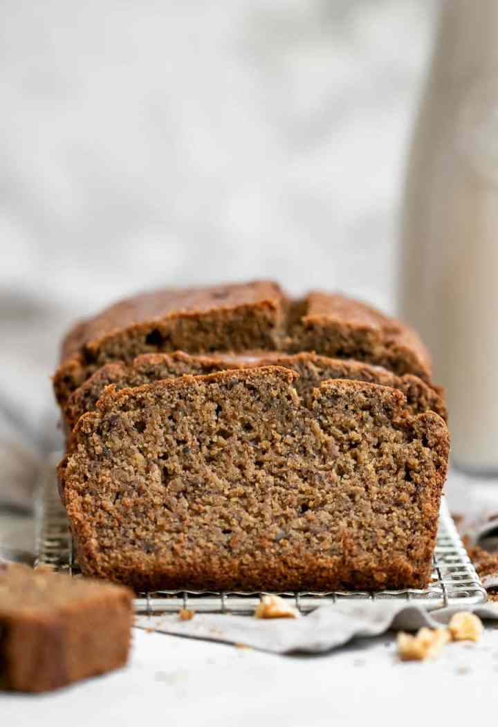 Banana bread with a glass of milk in the background.