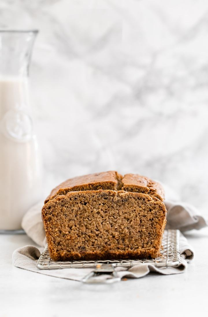 Healthy banana bread on a cooling rack with a jar of milk in the back.