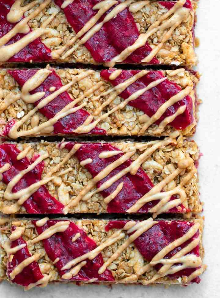 4 no bake granola bars with peanut butter and jam on top.