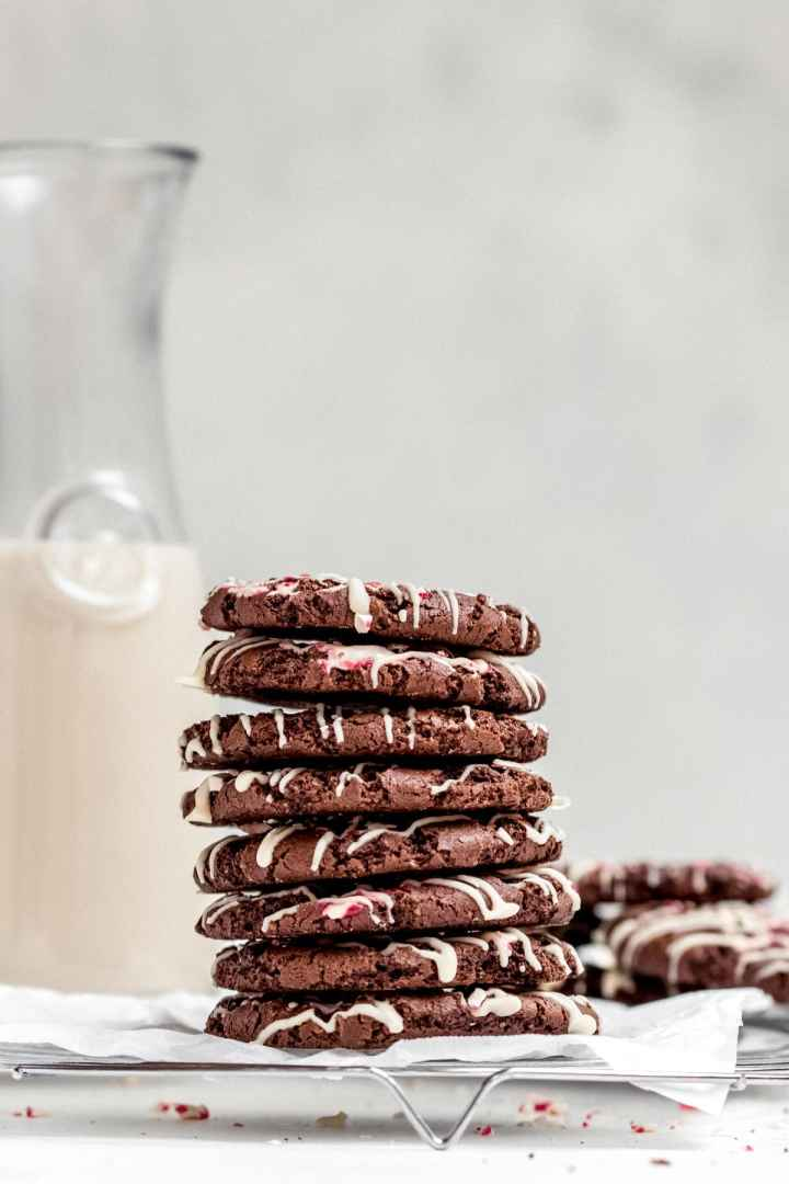 Stack of cookies with a jar of milk in the back.