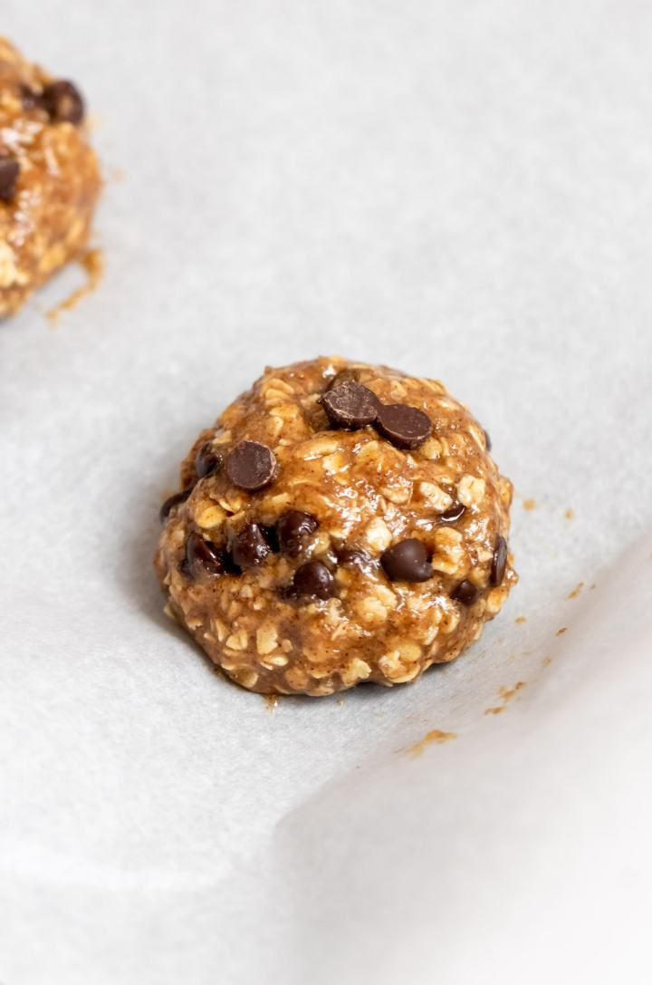 Uncooked vegan oatmeal chocolate chip cookie on a baking sheet.