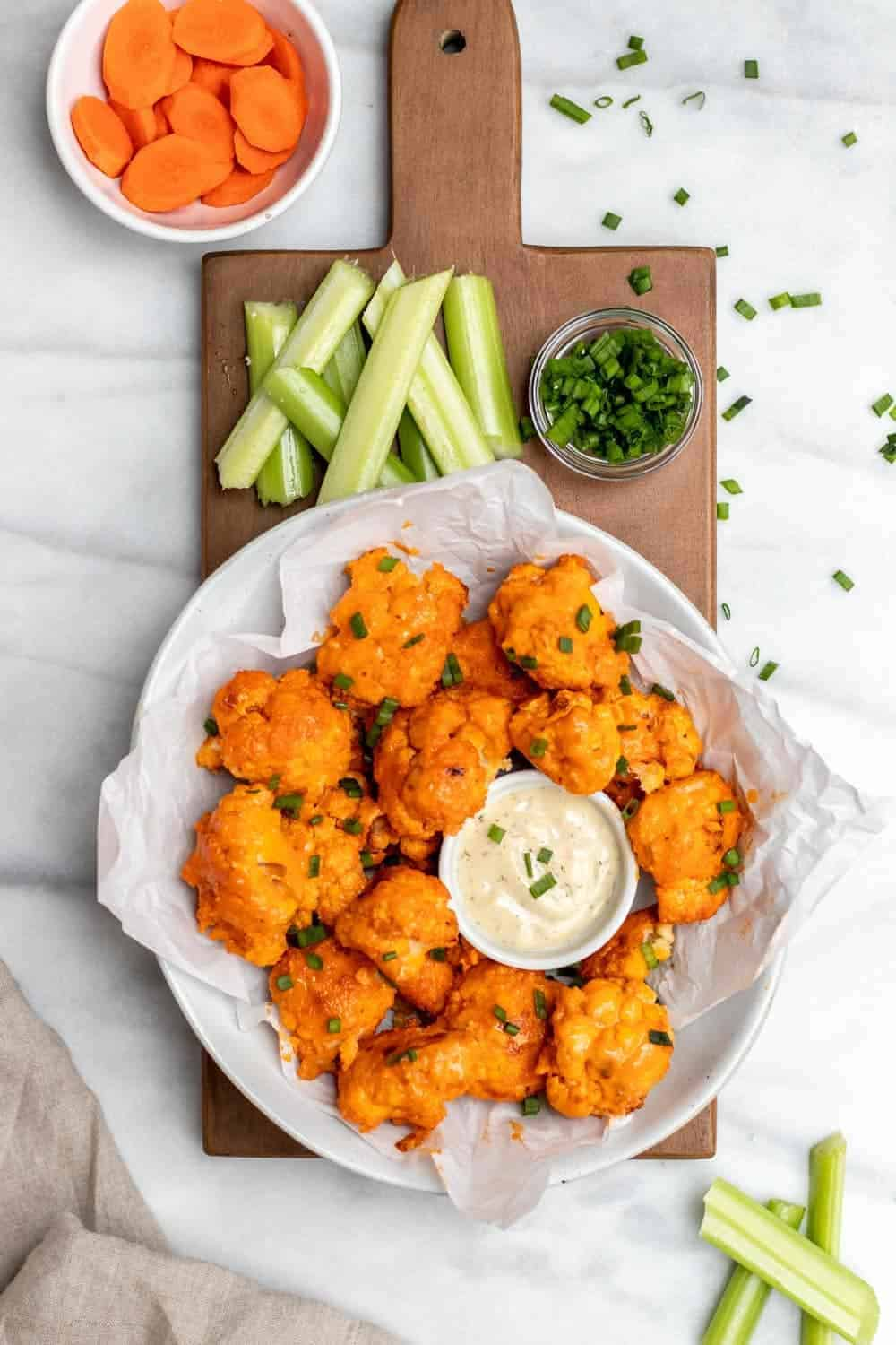 Final baked buffalo cauliflower on a wood board with celery and chives.