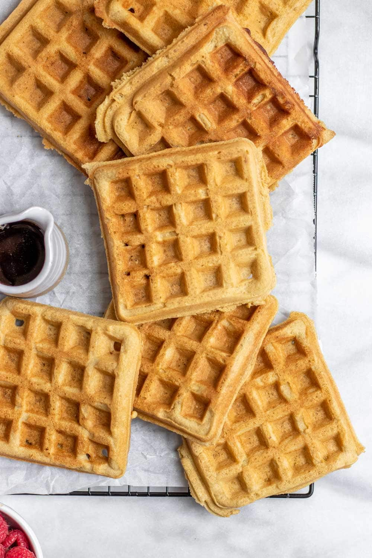 Vegan almond flour waffles cooling on a black rack.