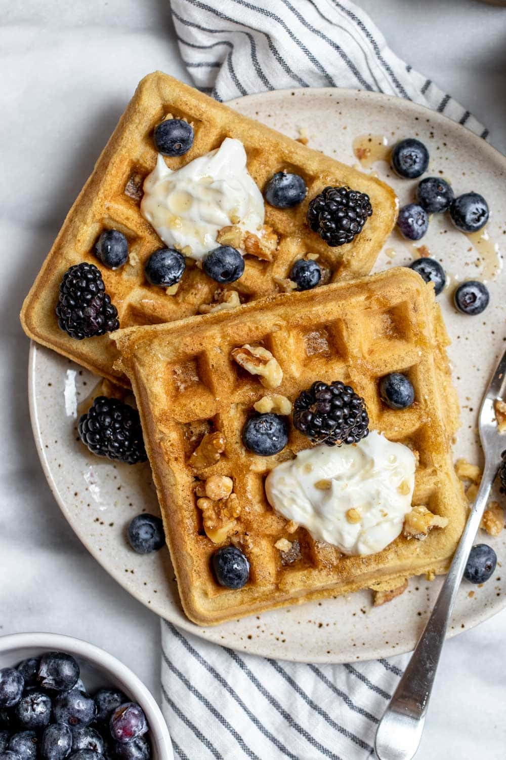 Two waffles on a plate with blueberries and maple syrup.