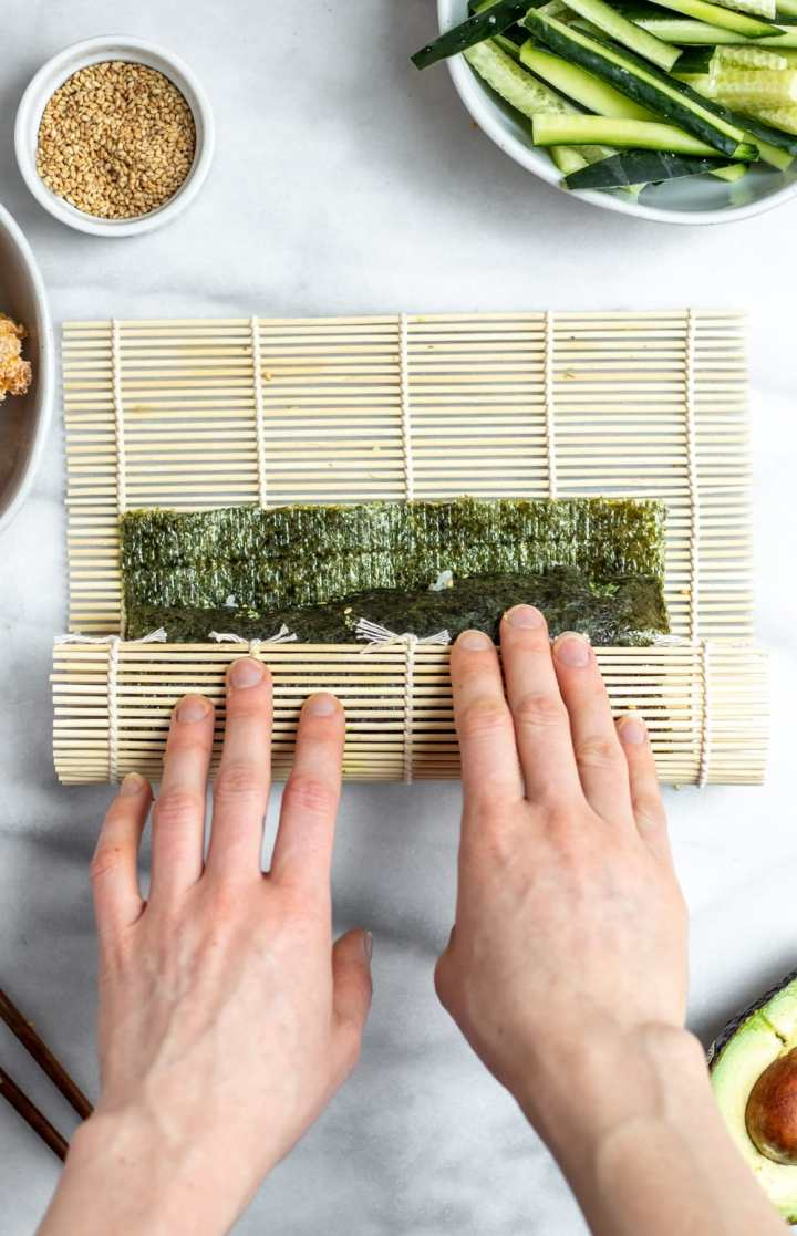 Rolling the sushi with a mat.