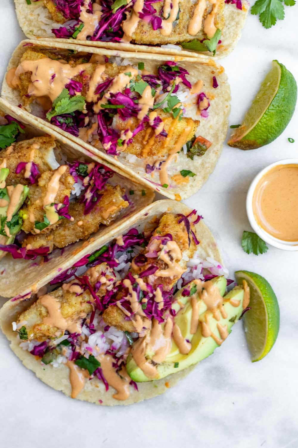 Baked cod fish tacos with spicy tahini dressing drizzled on top.