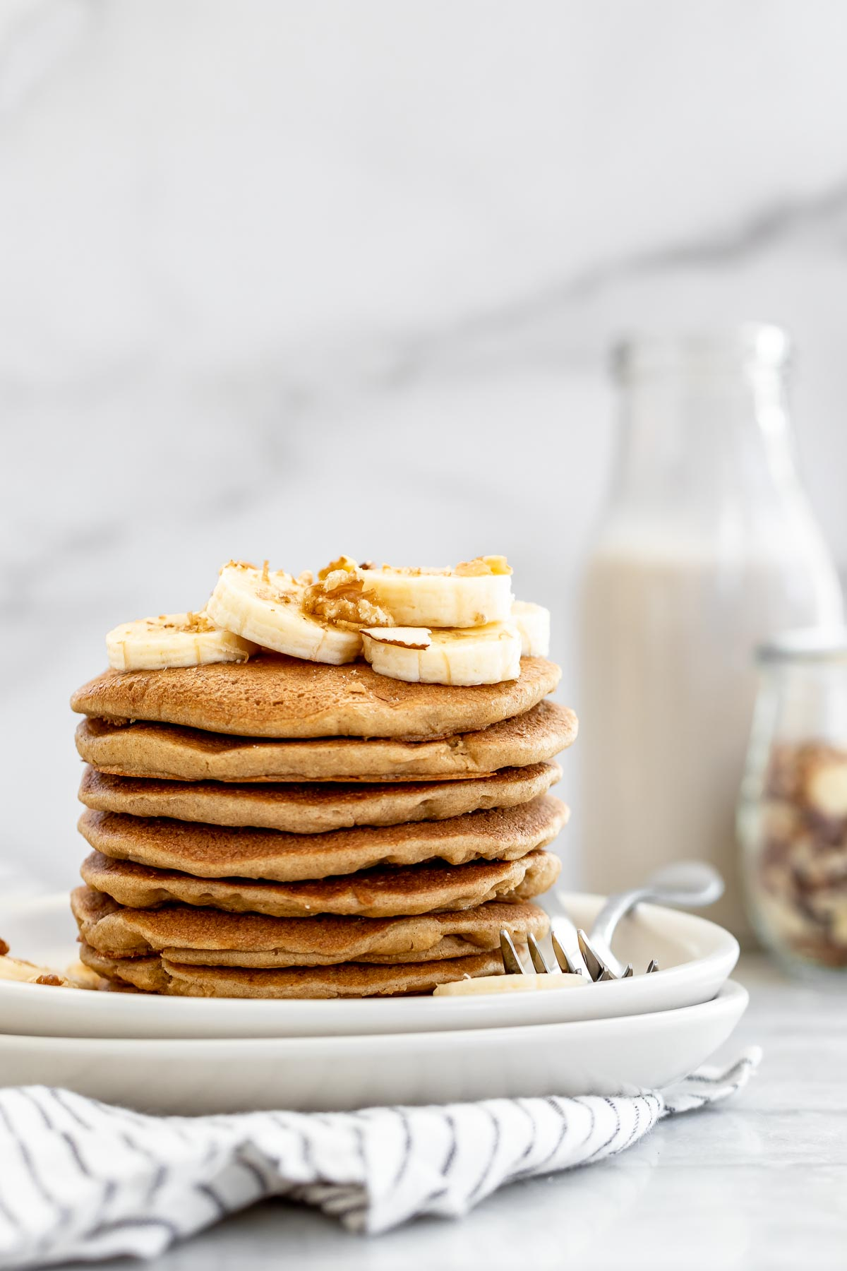 Gluten free banana pancakes with banana slices on top.