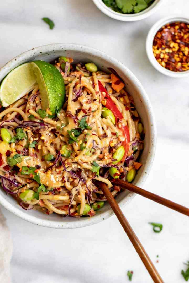 Up close image of the thai noodle salad in a bowl with chopsticks.