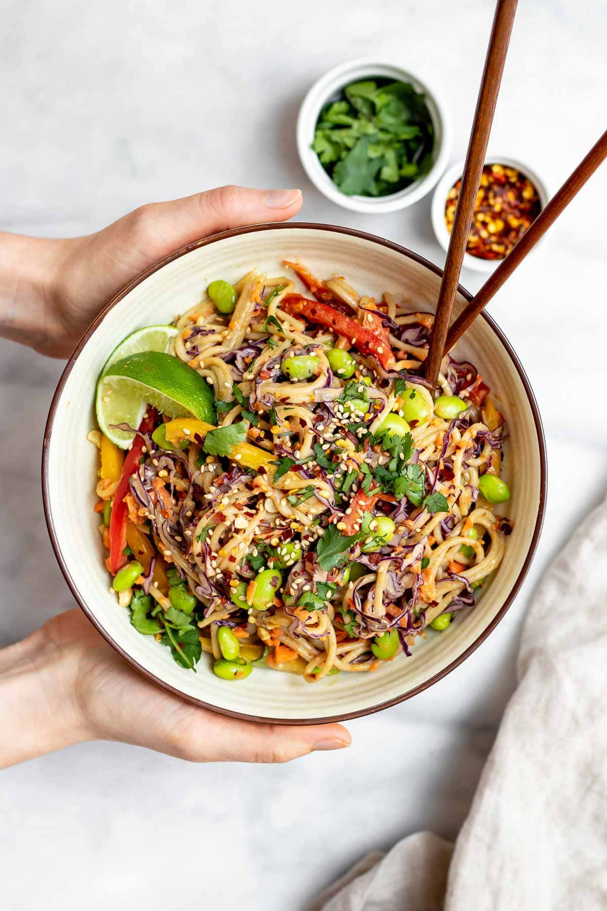 Two hands holding the thai noodle salad with chopsticks on the side.