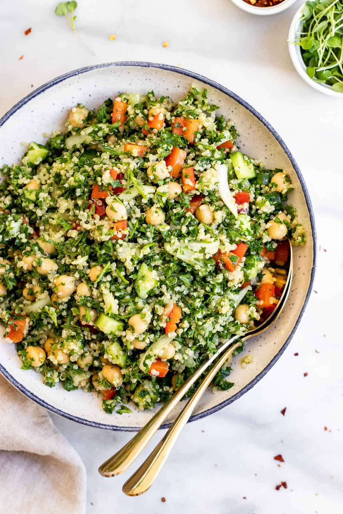 Overhead shot of the quinoa tabbouleh salad recipe with fresh parsley in a blue bowl.