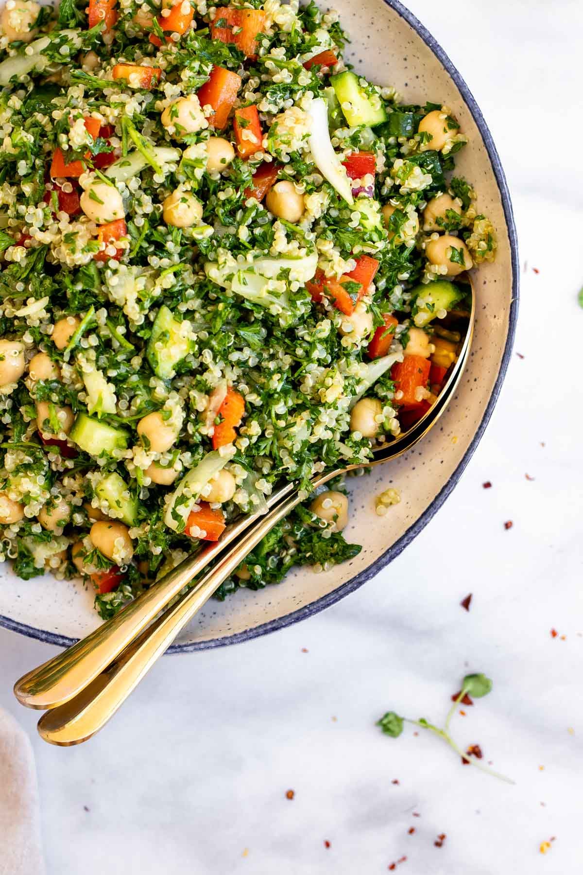 Final salad recipe in a large mixing bowl with two spoons on the side.