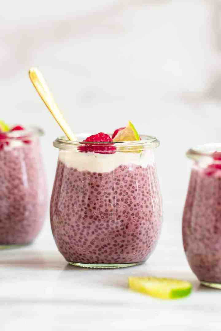 Vegan raspberry chia pudding in three small jars with lime and raspberries on top.