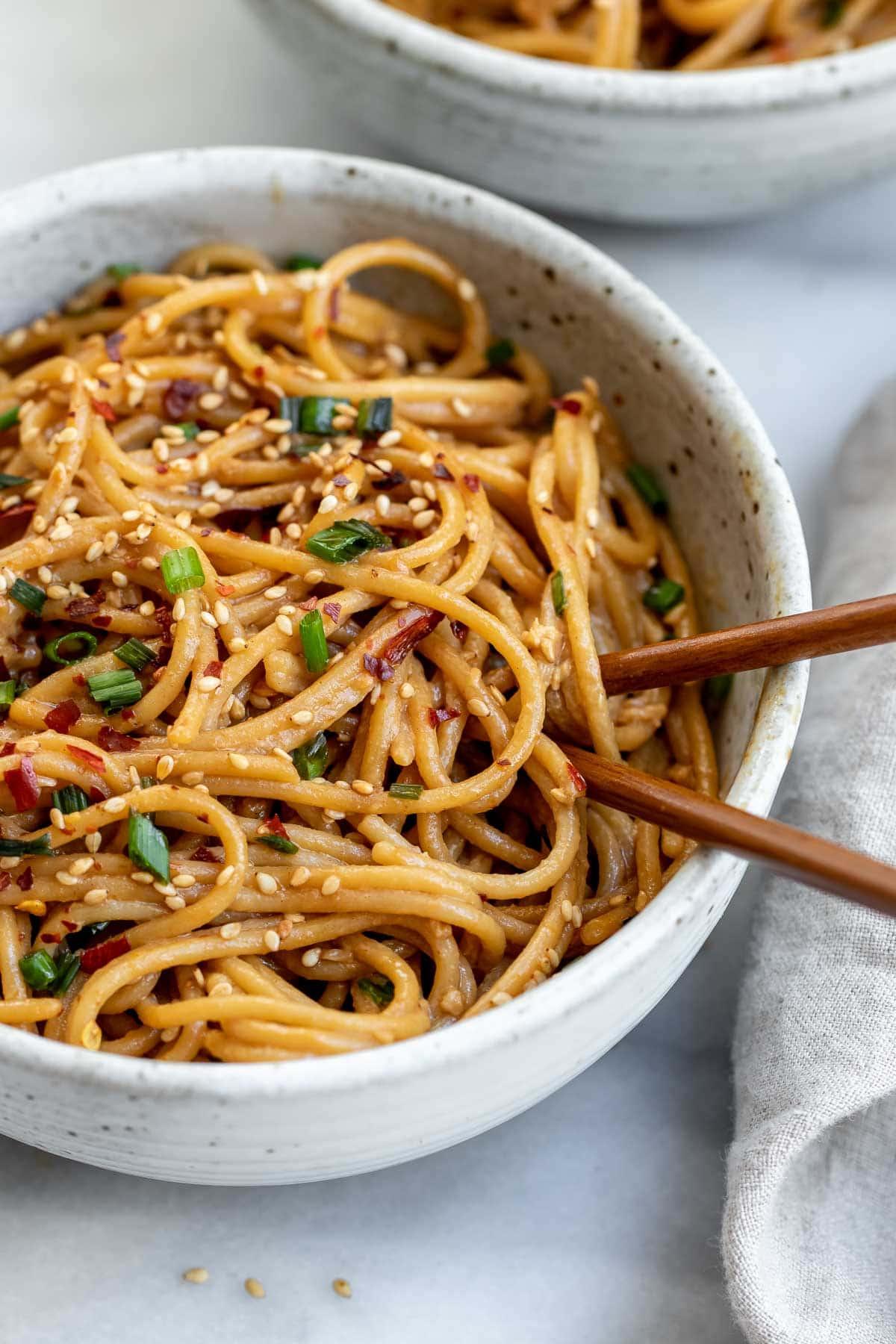 Up close image of garlic sesame noodles with chopsticks on the side.