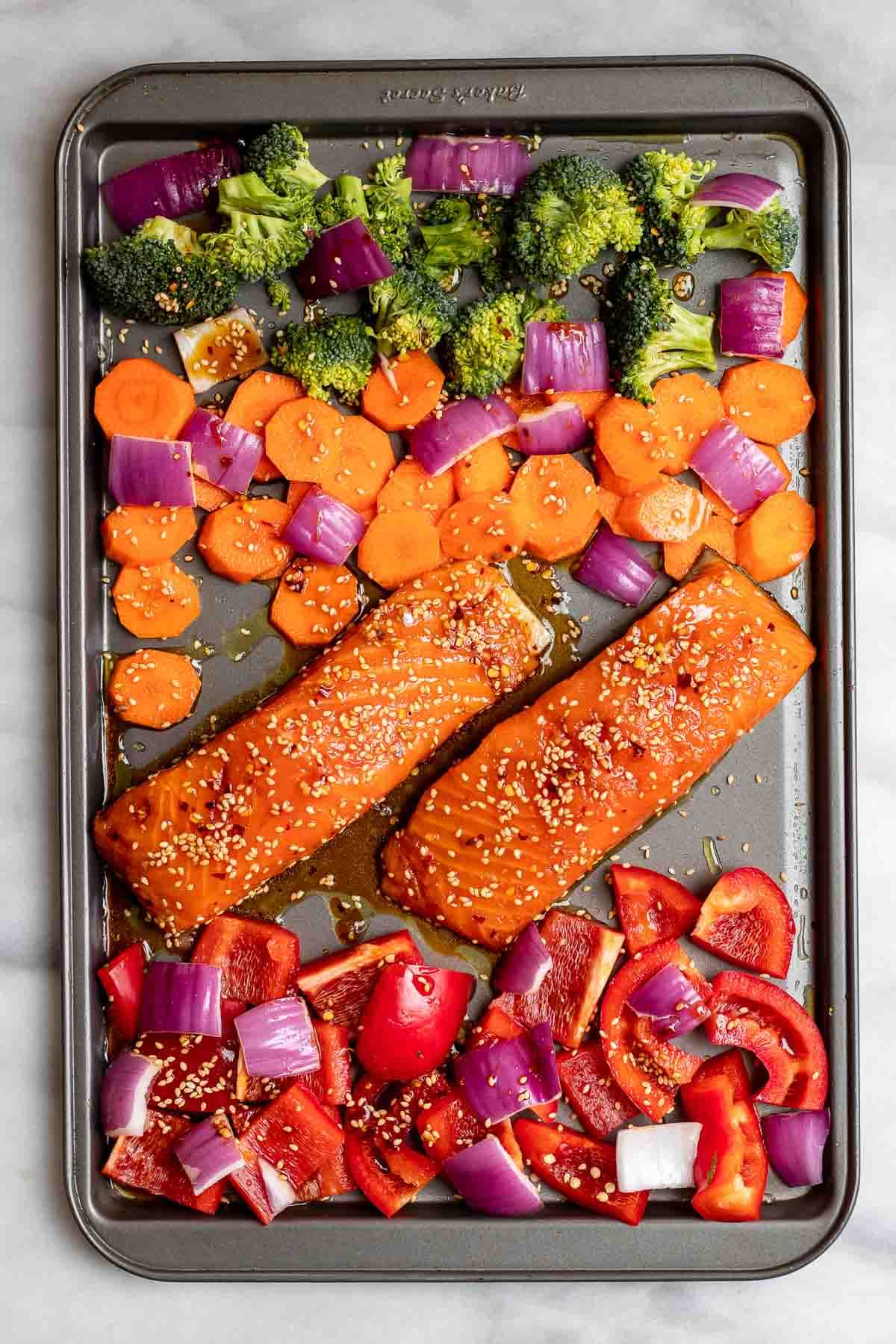 Salmon and veggies before going in the oven on a cookie sheet.