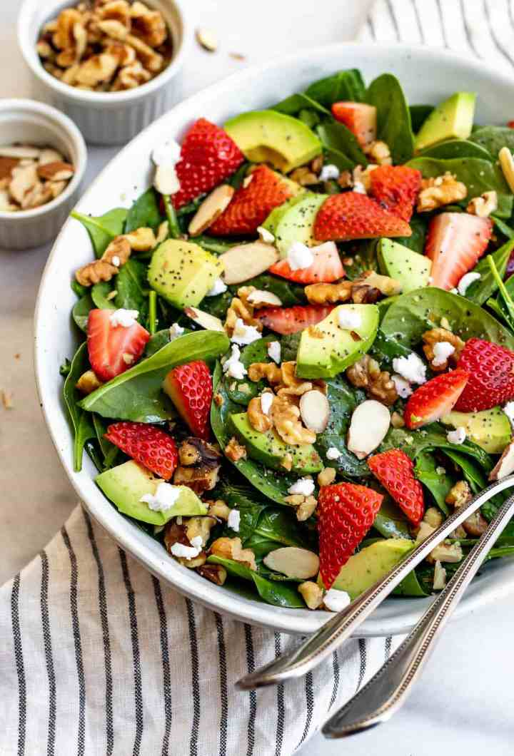 Spinach and strawberry salad in a large blue bowl with avocado and poppy seeds on top.