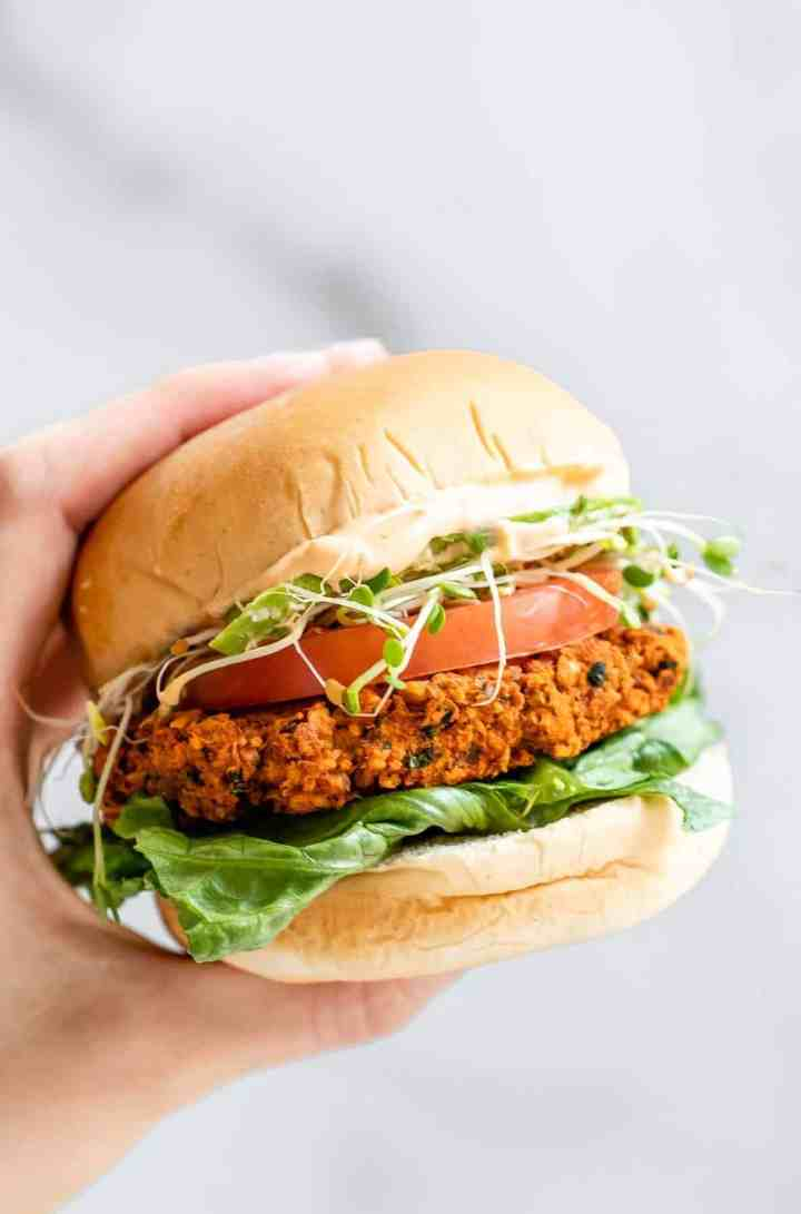 Hand holding up a chickpea burger with lettuce and tomato.