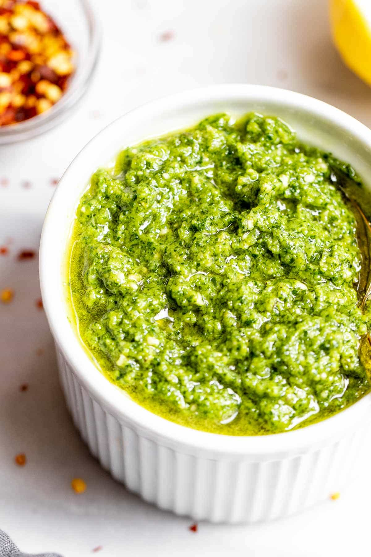 Up close image of pesto in a small white bowl.