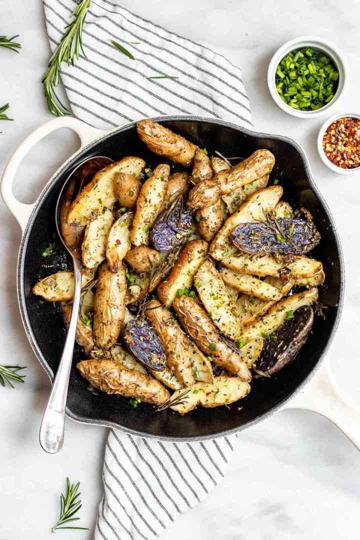 Overhead image of the final roasted fingerling potatoes with fresh herbs and a spoon on the side.