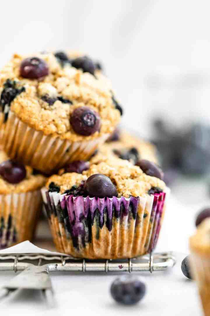 Blueberry muffins stacked on top of each other on a wire rack.