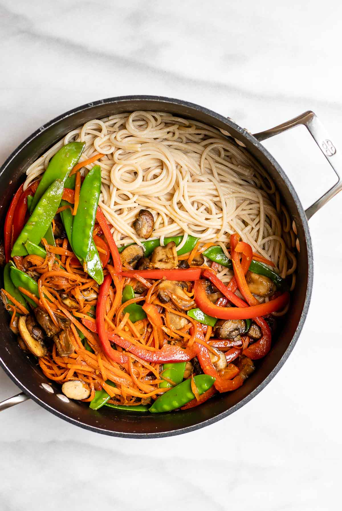 Cooked noodles and vegetables in a pot before getting mixed together.