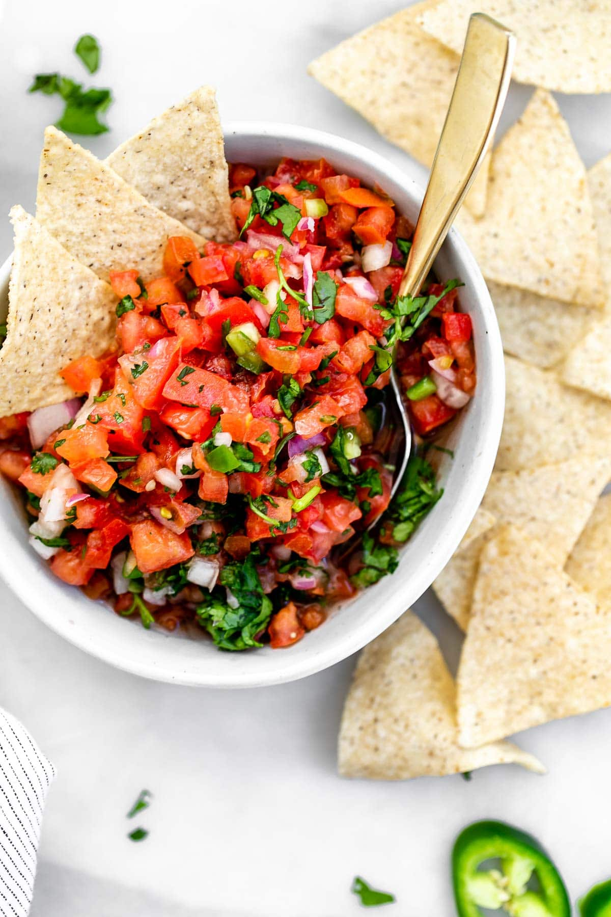 Overhead shot of the pico de gallo with a spoon on the side with chips.