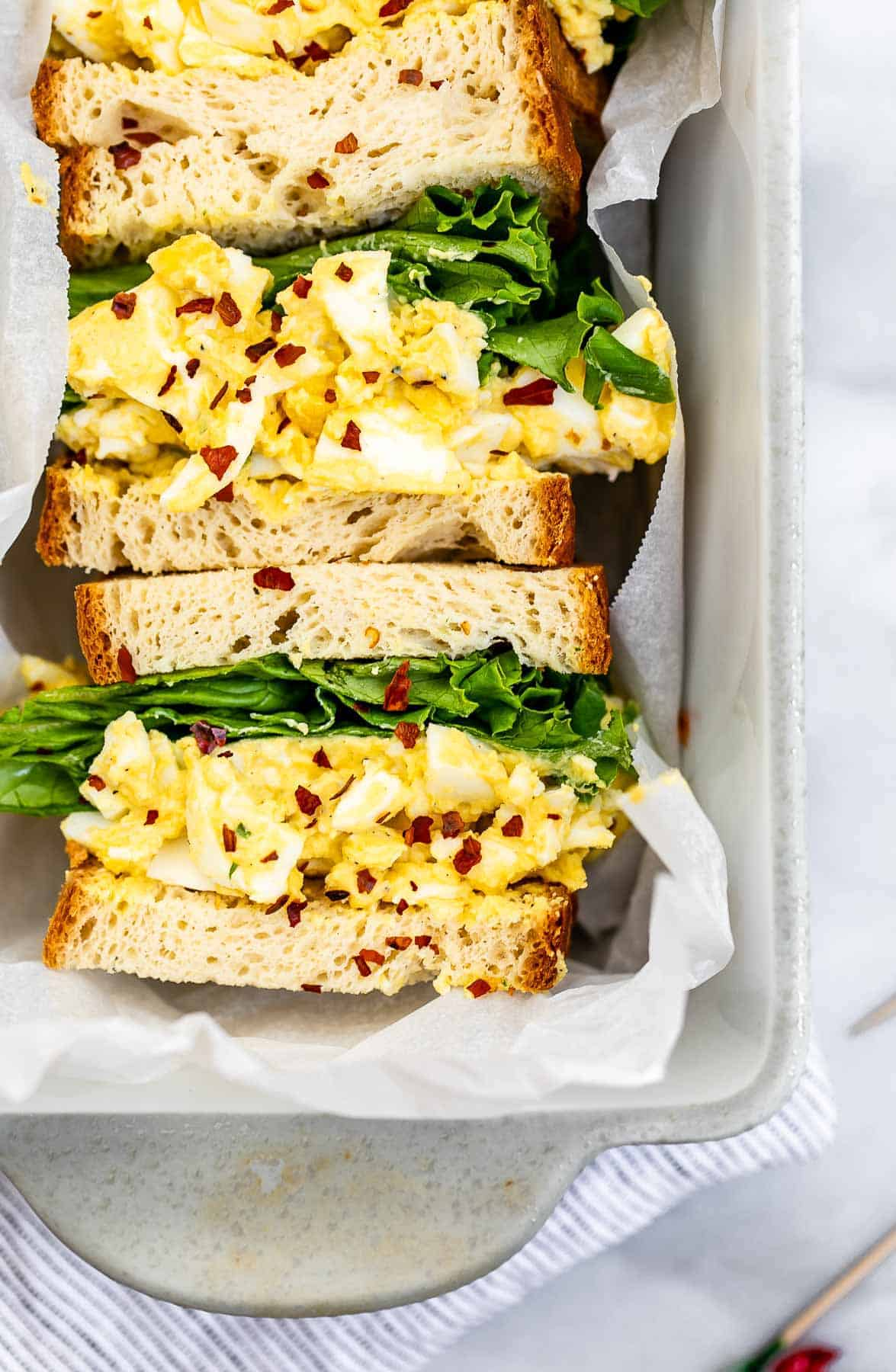 Up close image of the egg salad sandwich with red pepper flakes.