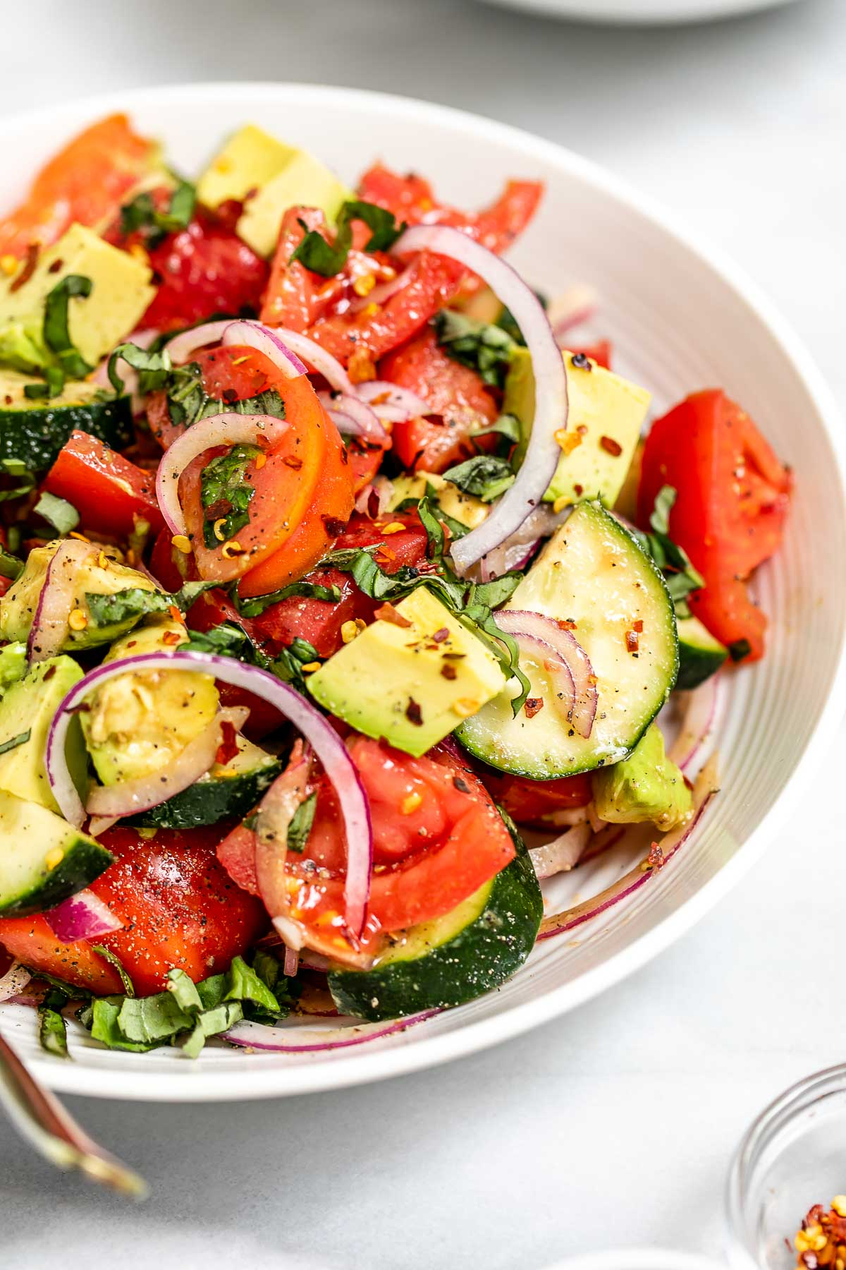 Angled view of the salad with avocado and basil.