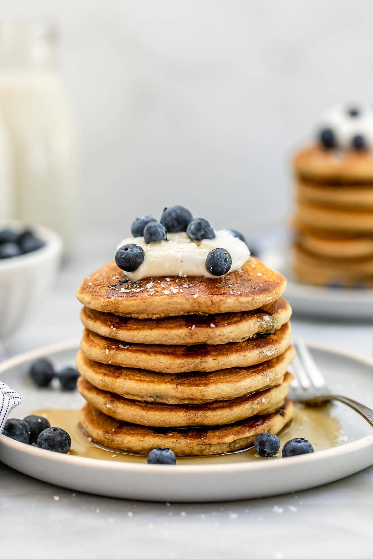Six vegan blueberry pancakes stacked on each other with yogurt on top.